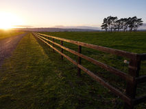 Road to nowhere. Road and fence leading straight into the sunset royalty free stock image
