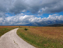 Road to nowhere. Mountain road under the cloudy sky royalty free stock images