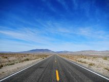 Road to nowhere USA. Landscape of road to nowhere with blue sky and mountains on the horizon. Picture of road in USA United States in California Stock Photo