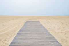 Road to nowhere wooden way sandy beach. Clouds royalty free stock image