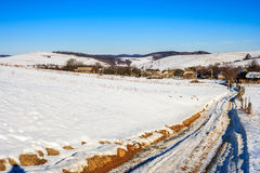 Road to old village along a snowy slope in winter Royalty Free Stock Image