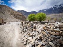Road to the overcast weather snowy mountain at distance along with the stone wall and few trees Stock Photos