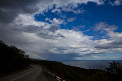 Road to the rainbow. Road along the sea under golybym sky cloud storm and rainbow Stock Photography