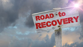 Road to Recovery. Wooden sign and sun braking thru dark skies royalty free stock photography