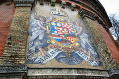 Road to Royal Palace with ancient mosaic Coat of Arms on Castle Stock Photo