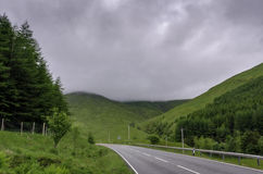 Road to Scottish Highlands. A wide angle shot of a road leading through the mountains of the Scottish Highlands. This photograph shows the green, grassy hills of stock photo