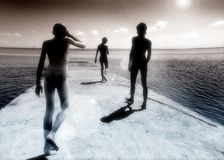 Road to sea. Three black figure go to the sea by the breakwater Royalty Free Stock Photos