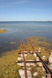 Road to the sea. Old rails for descent of a boat in water Stock Photography