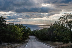 Road to the sea. The rays of the sun hiding behind clouds of light on water Stock Image