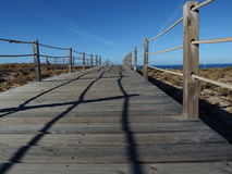 Road to the sea. Wooden walkway through the sand Stock Photography