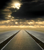 Road to the sky. Road vanishing to the horizon under sun rays coming down trough the dramatic stormy clouds royalty free stock photo