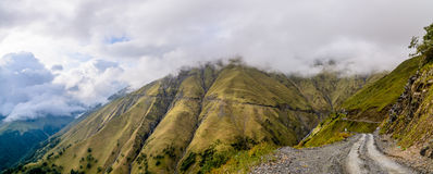 Panoramic shot of dangerous mountain road under mist and clouds Stock Photos