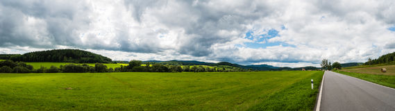 The road to the small ancient city. In Czech. The panoramic view of beautiful landscape with pasture, meadow, field, forest, road and church on horizon. Cloudy Stock Photography