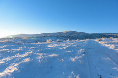 Road to the snowy mountain with sunset sunlight on hill Royalty Free Stock Photo