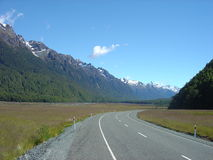Road To Somewhere. A road disappearing into the distance backed by a snow capped South Island mountain range Stock Photo