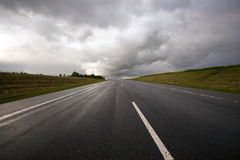 The road to a storm. The asphalted road to time of storm weather. Belarus Royalty Free Stock Image
