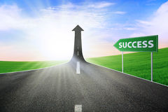 The road to success. A road turning into an arrow rising upward with a road sign of success, symbolizing the direction to success Stock Photography