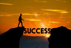 Road to success, Motivation, ambition, business concept. Man about to walk over SUCCESS word bridge between mountains. Yellow sky with sun flare, optimism stock image