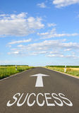 Road to success. Word success and arrow on countryside road receding into distance Royalty Free Stock Images