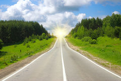 Road to the sun. Road through the wood, removed in the solar afternoon Royalty Free Stock Image
