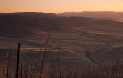 Road to the sun. Orange light of a rising sun over hills of the Siberian steppe Royalty Free Stock Images