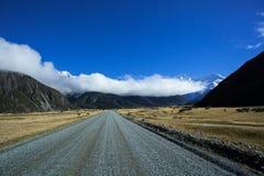 Road To Tasman Valley At Aoraki Mt. Cook National Park. Access to the Tasman Valley of Aoraki Mount Cook National Park, is a gravel road. Long big clouds Stock Photos