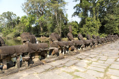 Road to temple, wood and river, ruins of statues, 12th century,  Cambodia Royalty Free Stock Photos