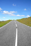 Road to the Top. Uphill rural road with grass verges on either side and a blue sky with clouds Royalty Free Stock Photos