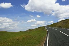 The Road to the Top. Uphill road in deserted countryside with grass verges either side on a blue sky with clouds. Set in the Brecon Beacons, National Park, Wales royalty free stock photos