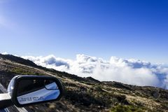 The road to the top of the Haleakala and side mirror of the car, MAUI, HAWAII stock image