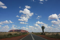 Road to Uluru, outback Australia. Road to Uluru (Ayers Rock), Australia and blue sky with few clouds Royalty Free Stock Images