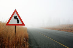 Road to the unknown. Tar road leading into thick mist with warning sign for curve Royalty Free Stock Images