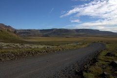 A Road to the Valley of Elves in Iceland. A gravel road to the valley of elves in Iceland with volcanic hills in the background Royalty Free Stock Images