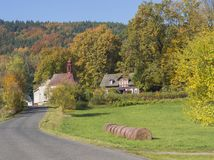 Road to the village chapel in autumn rural landscape with straw Stock Image