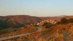 Road to the village. Evening view of narrow road and village houses with wind mill on the horizon in Karaburun, Turkey Royalty Free Stock Photography