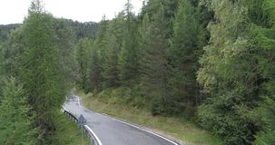 Road to the Village Santa Maddalena Dolomite. Amazing aerial shot of road in Dolomiti mountain on a cloudy autumn day. Flying above beautiful green forest in stock video footage