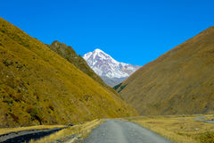 Road to village Sno, caucasus mountains, mountain river, snowy peak Mkinvari and road Royalty Free Stock Photography
