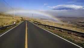 The Road to Waimea. Mauna Loa looms in the distance as rain clouds and a rainbow decorate the road from Hawi to Waimea on the Big Island of Hawaii stock photo