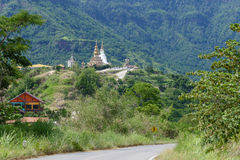 Road to 5 white buddha statue and buddhist pagoda on the hill Stock Images