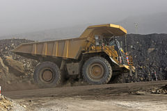 On the road. A 130 ton tiptruck emerges from the mist at an open cast coal mine, Westland, New Zealand stock image