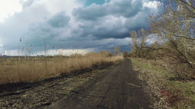 Road towards clouds. Driving on road with rain clouds to meet reeds stock footage