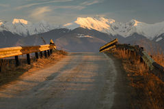Road towards the Mountains. Old road with rusty road fences pointing towards snowy mountains in background in warm orange light of sunset royalty free stock photography