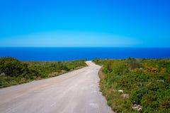 Road towards the sea coast  on Zante Island. Empty narrow paved asphalt road towards the Mediterranean sea on the coast and shore on Zante Island, Greece royalty free stock photo