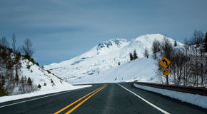 Road towards a snow capped mountain Stock Image
