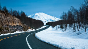 Road towards a snow capped mountain. A clean road towards a snow capped mountain. Also symbolizes the path towards a peak or towards qrowth Stock Images