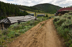 The Road Into Town. Dirt road leading into a Montana ghost town with a house, a garage, an old truck, a flotation mill, and another building in sight. Focus is royalty free stock images