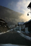 Road through town in mountains. Scenic view of road through town or village in mountains during winter sunset Royalty Free Stock Photography