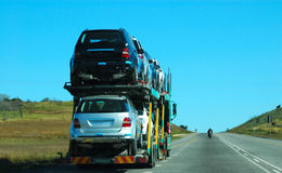 Road tractor. A big truck (road tractor) transporting luxury brand new cars driving on a freeway on the left lane behind a motorcycle in South Africa Royalty Free Stock Photo