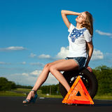 Road traffic accident. Beautiful girl waiting for help on the road stock image