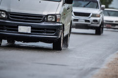 Road traffic driving in rain. Vehicles driving fast in rain on wet road Royalty Free Stock Image